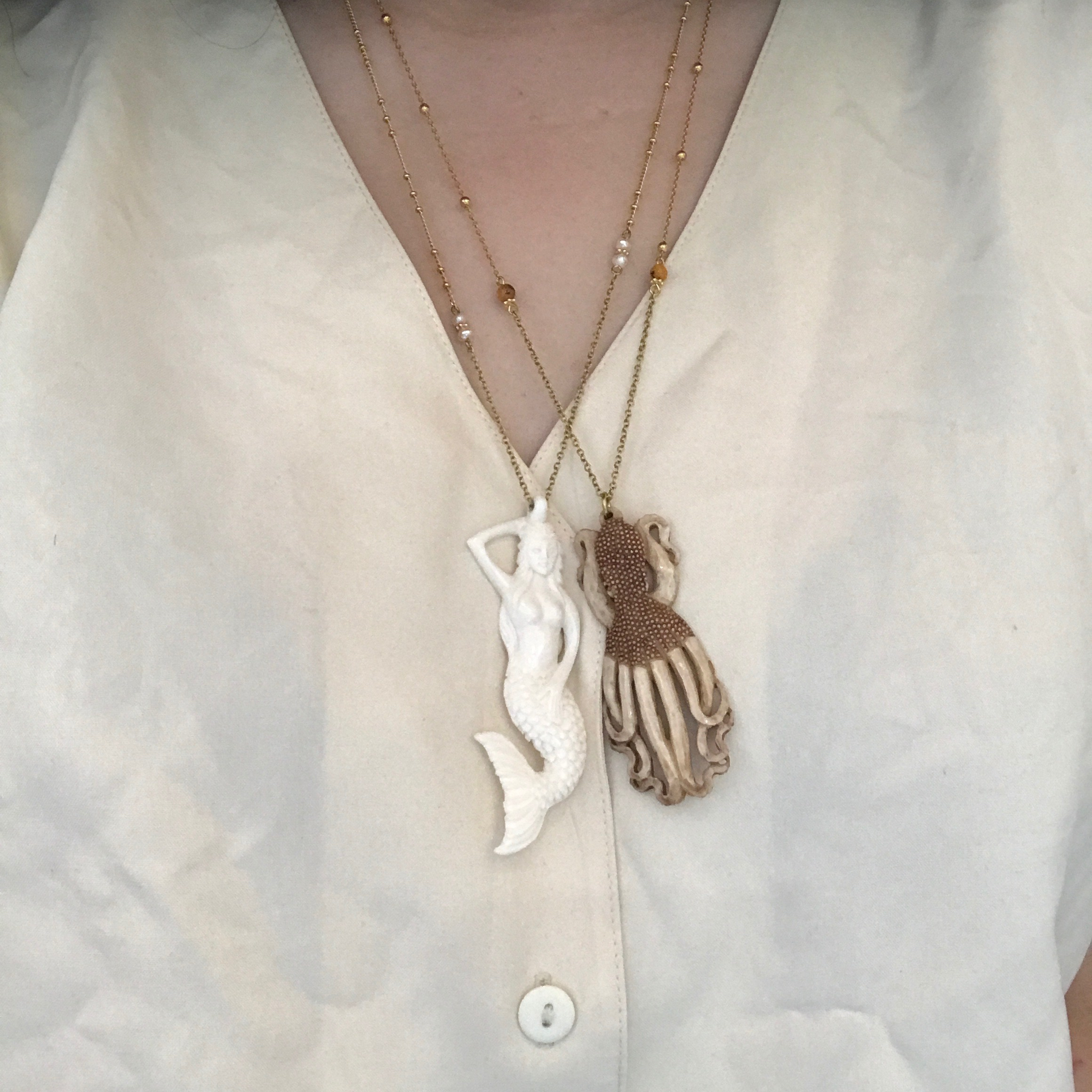 Mermaid and octopus made of bone on gold-plated necklace by Petra Reijrink Jewelry